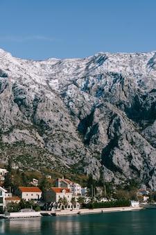 Felsige schneebedeckte berge über häusern im golf von kotor montenegro