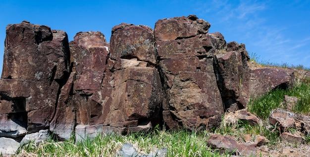 Felsiger abhang der roten wüste mit rauen gebrochenen steinen und gras