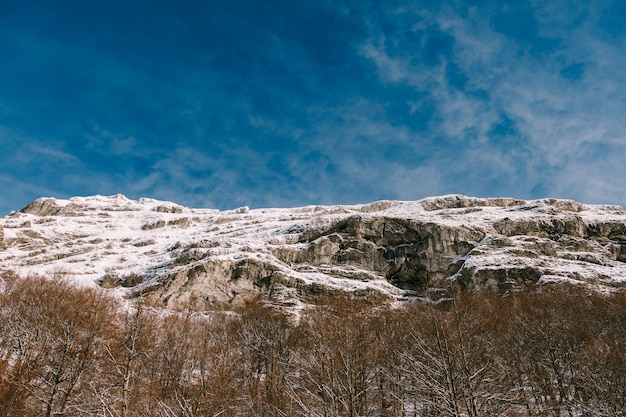 Felsiger schneebedeckter berggipfelblick von unten nach oben
