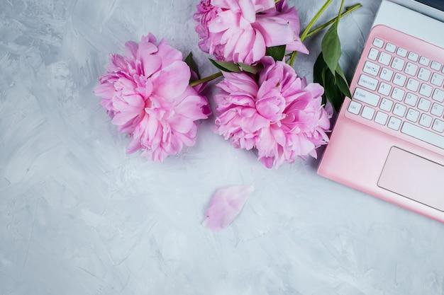Feminine geschäftsmodell mit rosa laptop und pfingstrosenstrauß, flatlay auf zement