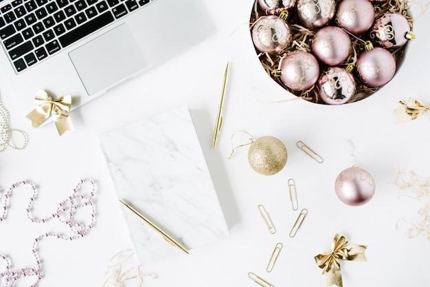 Femininer arbeitsbereich mit laptop, marmortagebuch, goldenem stift, weihnachtsdekoration, weihnachtskugeln, lametta, bogen auf weißem hintergrund.