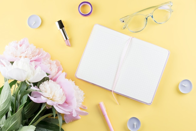 Femininer arbeitsbereich mit offenem leerem notizbuch, pfingstrosenblumen, brillen