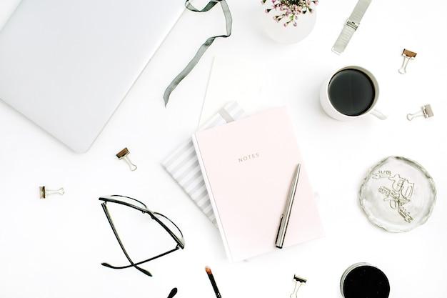 Femininer moderner home-office-schreibtisch mit pastellrosa notizbuch, gläsern, kaffeetasse, wildblumen und briefpapier auf weiß