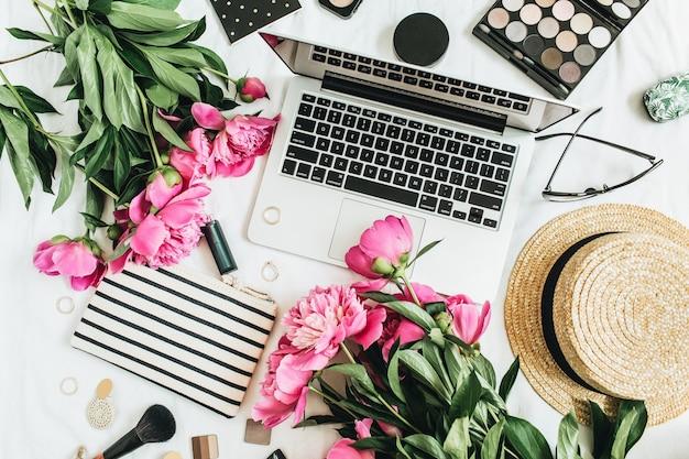 Femininer schreibtisch der flachen laienmode mit laptop, rosa pfingstrosenblumen, kosmetik, accessoires. sommerblumenhintergrund des lebensstils des draufsichtlebensraums.