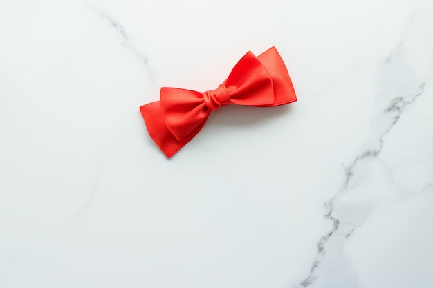 Feminines design des urlaubsdekors und rotes seidenband des flatlay-konzepts auf marmoransicht Premium Fotos