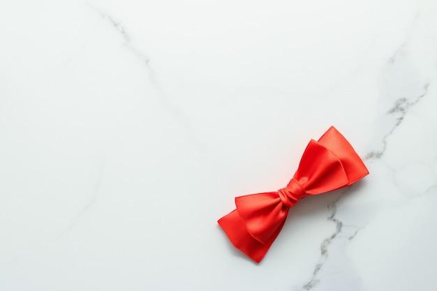 Feminines design des urlaubsdekors und rotes seidenband des flatlay-konzepts auf marmoransicht