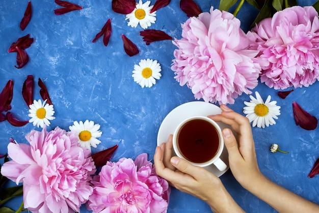 Feminines flatlay-modell mit frauenhänden, die tasse warmen tee auf blauem zementhintergrund halten, der durch blumen umgeben ist