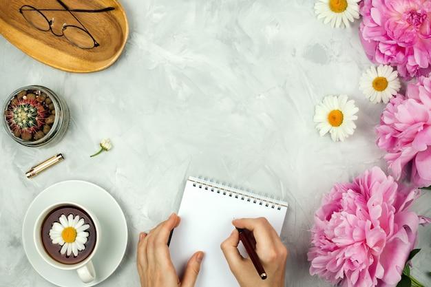 Feminines flatlay-modell mit rosa pfingstrosen, gänseblümchen, gläsern, tasse warmem tee, kaktus und weiblichen händen, die im notizbuch auf zementhintergrund mit copyspace schreiben
