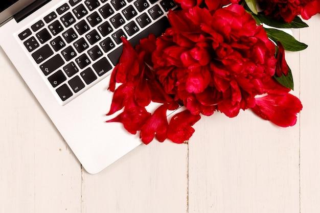 Feminines geschäftsmodell mit rosa laptop, pfingstrosenstrauß
