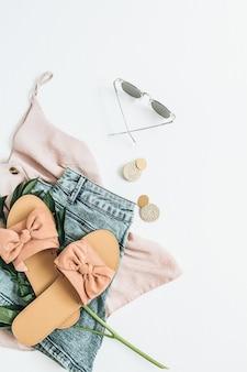 Feminines modekonzept mit weißer pfingstrosenblume, hausschuhen, sonnenbrille, ohrringen, shorts, t-shirt auf weißer oberfläche