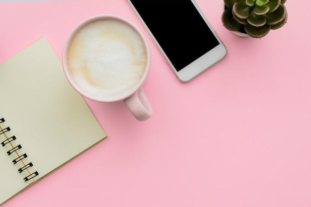 Feminini schreibtischarbeitsplatz mit smartphone, leerem notizblock, kaktus, tasse kaffee auf rosa hintergrund. flach liegen, draufsicht