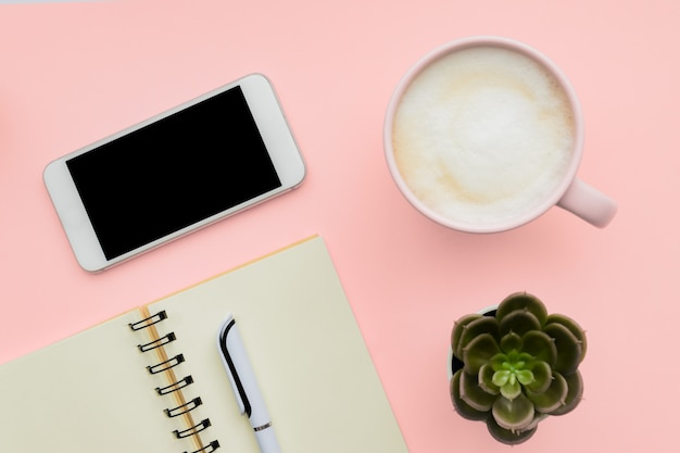 Feminini schreibtischarbeitsplatz mit smartphone, leerem notizblock, stift, tasse kaffee auf rosa wand. flach liegen, draufsicht