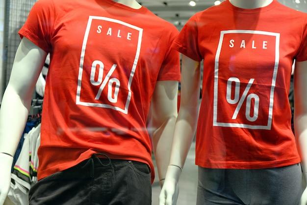 Fenster der boutique mit zwei schaufensterpuppen in t-shirts mit schildern werbung verkauf für sportbekleidung.