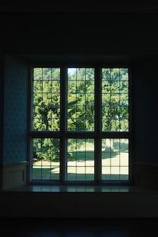 Fenster einer dunkelkammer mit grüner gartensommeransicht.