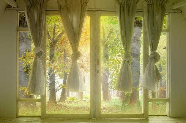 Fenster mit dem vorhang in einem verlassenen haus mit einem wald