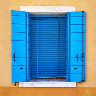 Fenster mit geschlossenem blauem fensterladen auf gelber wand.