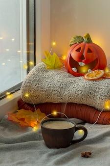 Fenster mit halloween-dekoration. kürbis mit einer kerze. in der nähe ist eine tasse heißen kaffee.