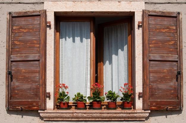 Fenster mit holzläden und blumentöpfen