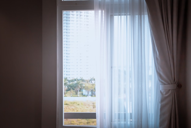 Fenster mit vorhängen oder vorhang blind durch das bett, innendekorationskonzept.