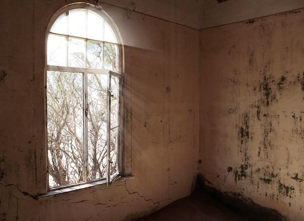 Fenster ohne glas und schmutzige wände in einem verlassenen haus