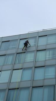 Fensterglasreiniger, der außerhalb des gebäudes arbeitet