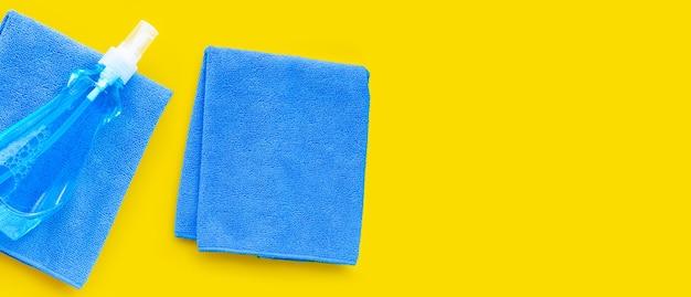 Fensterreiniger in plastikflasche mit blauen handtüchern