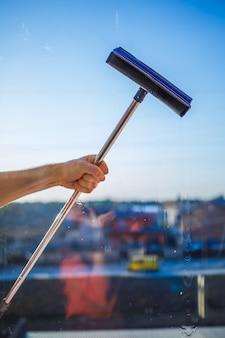 Fensterreinigung in hochhäusern, häuser mit einer bürste. reinigungsbürste für fenster. großes fenster in einem mehrstöckigen gebäude, reinigungsservice. staubentfernung und glasreinigung.