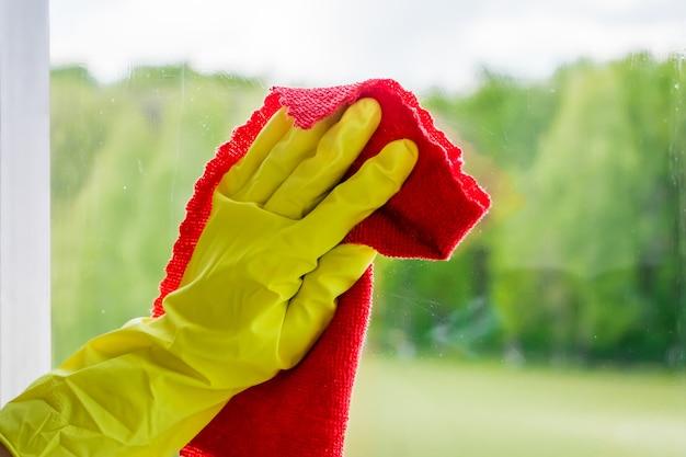 Fensterreinigung und haushaltsreinigung. die haushälterin in handschuhen wäscht und wischt schmutziges glas ab.