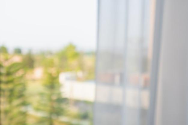 Fenstervorhang mit abstraktem unschärfehintergrund des grünen gartens