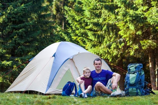 Feriencamping. vater zeigt seinem sohn etwas in der ferne, wie er sich in der nähe des zeltes ausruht, nachdem er im wald gewandert ist. reisen und aktivitäten im freien. glückliche familienbeziehungen und gesunder lebensstil.