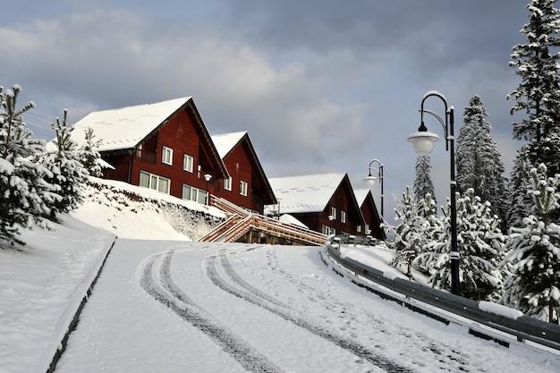 Ferienhaus aus holzhütten im ferienort in den bergen, bedeckt mit frischem schnee im winter. schöne winterstraße nach dem schneefall.