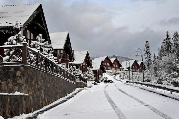 Ferienhaus aus holzhütten im ferienort in den bergen, bedeckt mit frischem schnee im winter. schöne winterstraße nach schneefall.