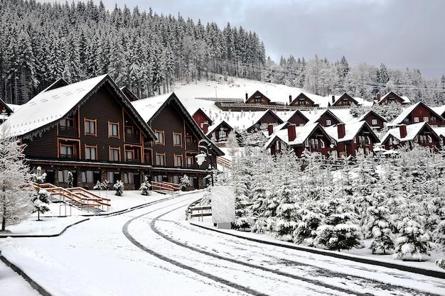 Ferienhaus aus holzhütten im ferienort in den bergen, bedeckt mit frischem schnee im winter. winterstraße nach schneefall.