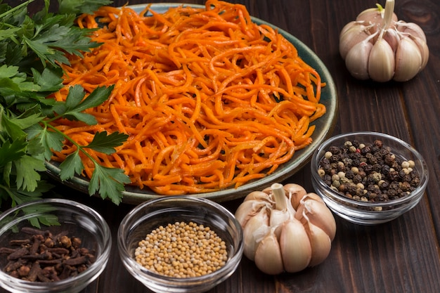 Fermentierte karotten in platte. gewürze, knoblauch und petersilie auf dem tisch. natürliches heilmittel zur stärkung des immunsystems. nahansicht