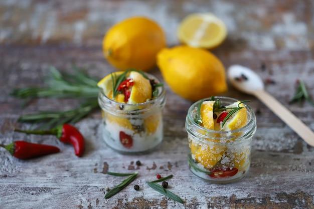 Fermentierte zitronen in gläsern mit salz, chili und rosmarin