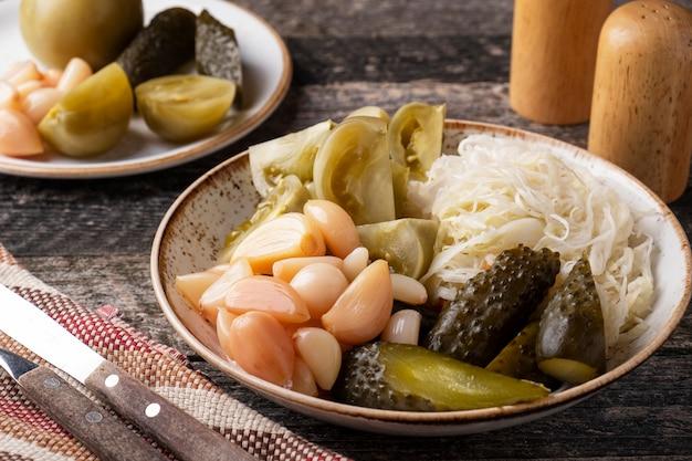 Fermentierter kohl, gurken, tomaten und knoblauch auf einem teller. kalter snack