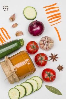 Fermentierter kürbisaufstrich im glas rohes gemüse und gewürze karotten knoblauch zwiebeln tomaten sternanis chili pfefferkorn
