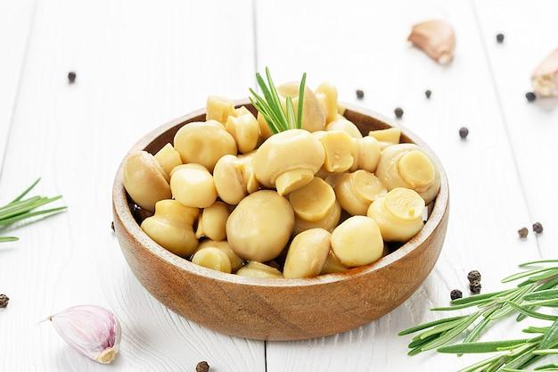 Fermentiertes essen. eingemachte champignons in einer holzschale auf einem weißen holztisch.