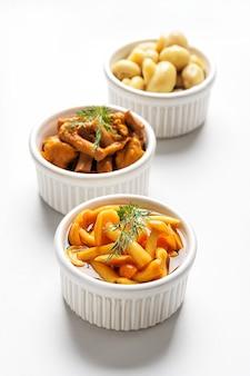 Fermentiertes essen. eingemachte pilze in schalen auf weißem hintergrund.