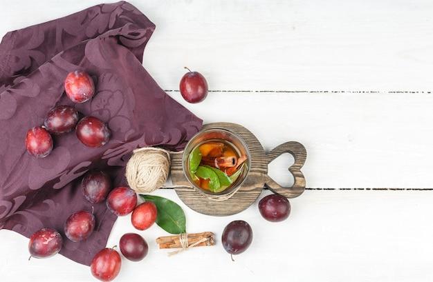 Fermentiertes getränk von oben mit zimt, clew und burgunderfarbener tischdecke auf weißer holzbrettoberfläche.