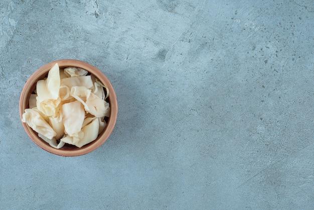 Fermentiertes sauerkraut mit karotten in einer schüssel auf dem blauen tisch.