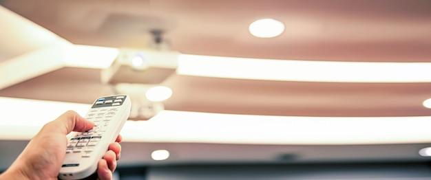 Fernbedienung schaltet die decke des digitalen overheadprojektors im sitzungssaal ein.