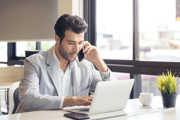 Fernbeschäftigung oder studium ist ein konzept. porträt eines jugendlichen, fröhlichen unternehmers, der einen anruf tätigt, während er in einem zwanglosen büro an einem laptop arbeitet.