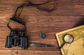 Fernglas, Kompass und Messer mit Mikroskop auf Vintage Karte