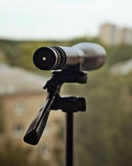 Fernglas oder teleskop auf stativ steht am fenster. überwachungs- und peeping-konzept.