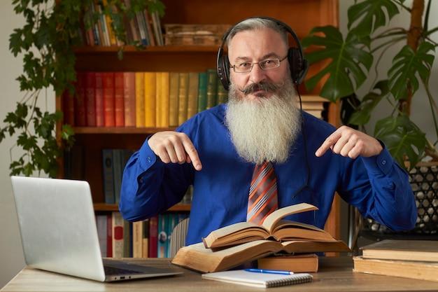 Fernlernkonzept. lehrer professor tutor in kopfhörern unterrichtet disziplin online. reifer bärtiger mann beantwortet die frage des lehrers durch laptop.