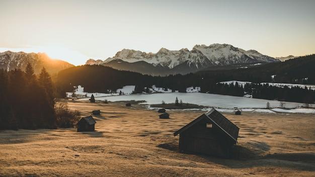Fernschuss eines tals mit einem hüttenhaus und hohen schneebedeckten bergen