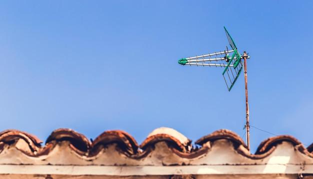 Fernsehantenne auf dem alten dach mit blauem himmel