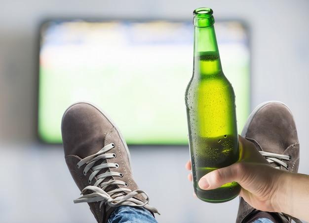 Fernseher an der wand und eine flasche bier