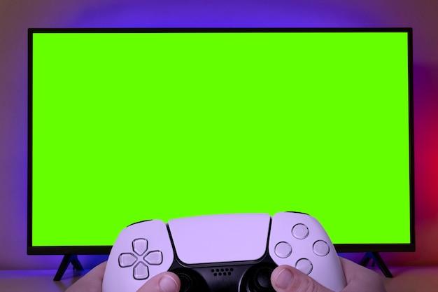Fernseher mit grünem bildschirm zum zuschneiden mit gamecontroller